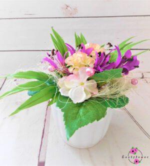 Topfgesteck mit lila-rosa Blüten im weißen Topf